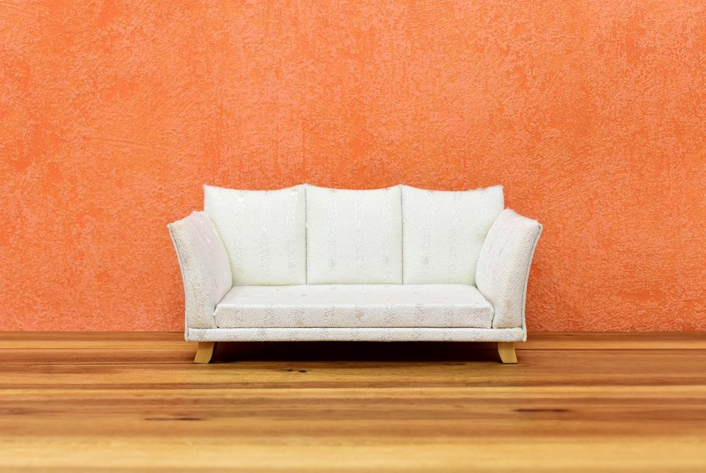 Couch in front of Orange Wall