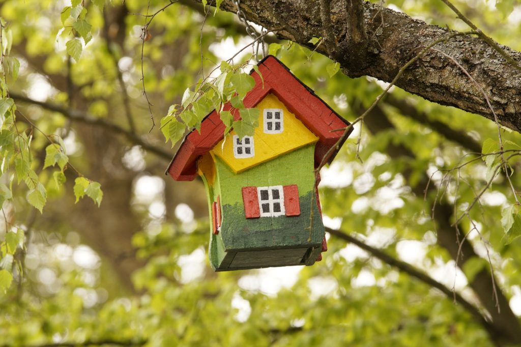 A multicolored birdhouse hanging from a tree