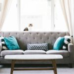 Grey couch with teal pillows