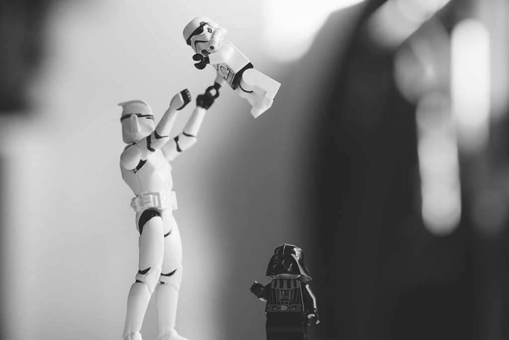 A stormtrooper action figure throwing a smaller stormtrooper action figure into the air