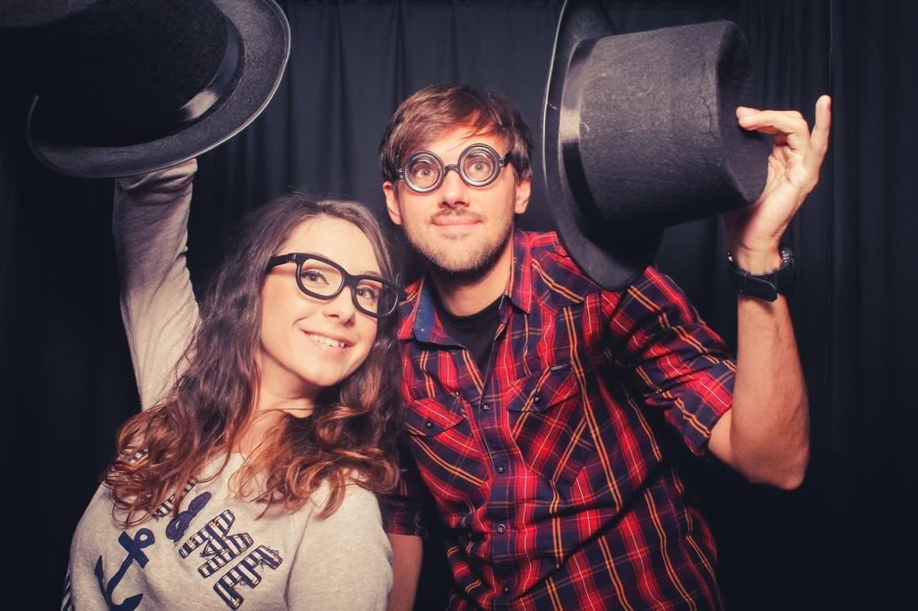 "Two ""geeky"" looking people holding up hats"