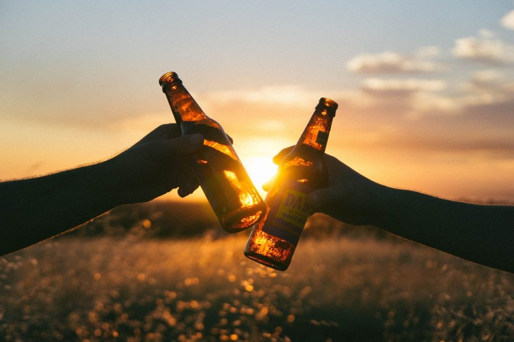 Two people clinking beer bottles together in front of a sunset