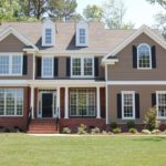A beige country style house with green lawn
