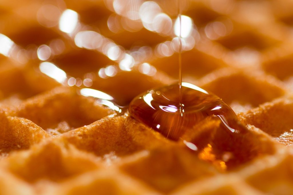 Maple syrup being poured on a waffle