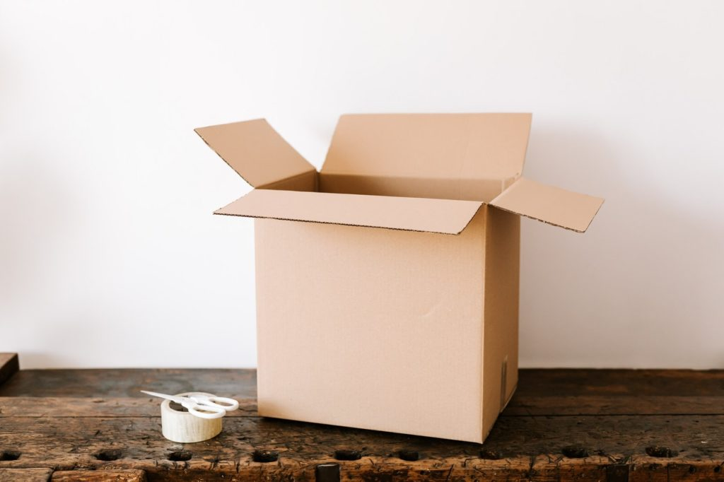 Open brown box on floor with packing tape and scissiors