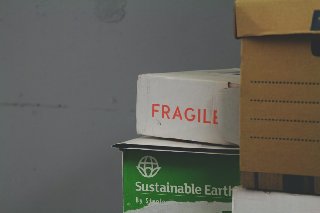 """Boxes stacked up, one says """"fragile"""" in red"""